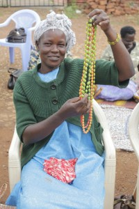 Uganda woman, Rupina, displays paper beaded necklace.