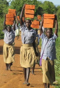 Northern Uganda students ferrrying bricks to help build classrooms