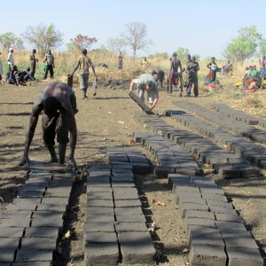 Agwata community and Uganda volunteers make bricks at northern Uganda school