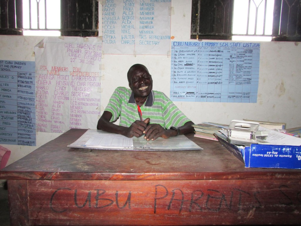 Deputy Headmaster Okello Okello at his desk in the school office. It is typical in Uganda to have many handmade posters on the office wall with statistics and information about the school's enrollment, teacher names, School Management Committee names, pupil count by grade, and so on.